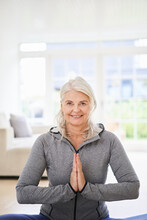 Smiling Senior Woman With Hands Clasped Exercising At Home