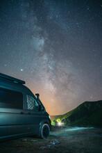 Camper Van Parked Near Mountain Against Star Sky