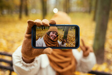 Young Woman Showing Selfie On Mobile Phone In Autumn Park