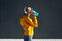 Female Athlete Wearing Headphones Drinking Water While Standing Against Gray Wall