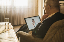 Female Doctor Consulting Online To Male Patient At Home