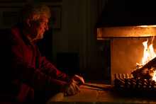 Smiling Senior Man By Fireplace At Home