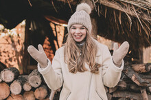 A Beautiful Young Girl Of Model Appearance Dressed In Winter Clothes Shows Hands In Mittens And Laughs On The Background Of Firewood