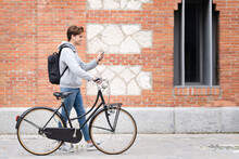 Smiling Man On Video Call Wheeling Bicycle By Building