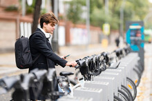 Young Man Standing Sharing Electric Bicycle Parking Station In City