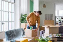 Young Man Packing Cardboard Box With Adhesive Tape In Living Room At New Home