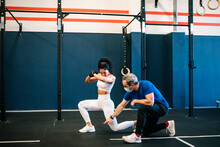 Male Instructor Training Female Athlete In Gym During COVID-19