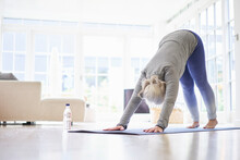 Active Senior Woman Practicing Yoga On Mat In Living Room At Apartment