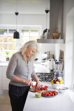 Retired Senior Woman Cutting Strawberries In Kitchen At Home