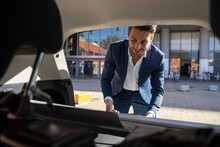 Smiling Businessman Taking Luggage From Taxi Trunk