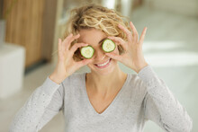 Playful Young Woman Standing Covering Her Eyes With Cucumber