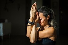 Mature Woman Practicing Yoga With Twisting Arms At Home On Sunny Day