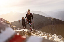 Sportsman And Woman With Hiking Pole And Backpack Walking On Mountain Path Of Bschiesser At Tyrol, Austria