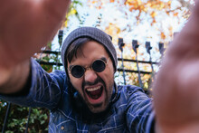 Young Man With Mouth Open Gesturing In Public Park