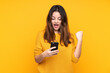 Young caucasian woman isolated on yellow background surprised and sending a message