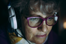 Close-up Of Senior Teacher Wearing Headphones While Working At Home