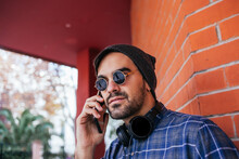 Fashionable Young Man Wearing Sunglasses On Phone Call Against Brick Wall
