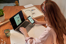 Female Artist Sharing Photograph Of Drawing Online Through Laptop At Desk In Home
