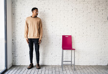 Mid Adult Man Wearing Eyeglasses Standing By Chair Against White Brick Wall