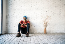 Man Wearing Knit Hat Day Dreaming While Sitting By Dried Plat Vase Against White Brick Wall
