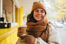 Smiling Young Woman Looking Away With Disposable Coffee Cup At Street Cafe During Winter