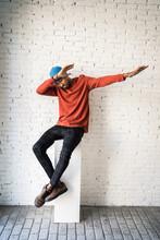 Man Dabbing While Sitting On Pedestal Against White Brick Wall
