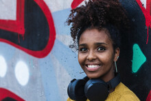Happy Afro Young Woman With Headphones Against Painted Wall