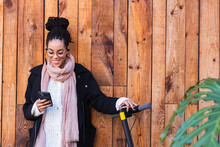 Beautiful Female Millennial Using Smart Phone By Electric Push Scooter Against Wooden Wall