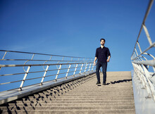 Businessman Walking On Staircase During Sunny Day