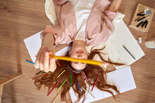 Playful Female Artist Showing Colored Pencil While Lying On Floor In Living Room