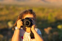 Child Looking Through DSLR Camera Taking Photo Of Viewer
