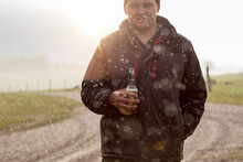 Young Man Having A Beer In The Rain