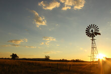 Windmill Silhouette On A Farm At Sunset