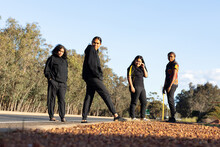 Four Teenagers Dressed In Black Standing On The Edge Of A Road