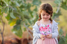 Little Girl Wearing Pink Floral Dress Self-absorbed In The Outdoors