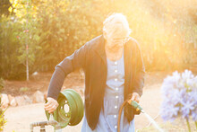 Golden Light Flare Over Old Woman Turning Off Tap For Watering Garden