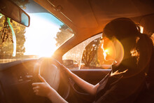 Teen Girl Driving Car With Lens Flare