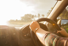 Woman's Hands On A Car Steering Wheel With Sun Flare On Highway