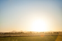 Glow Of Setting Sun Shining Over Farm Paddock And Bulga Hills