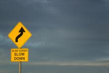 Blind Corner Slow Down Road Sign Against Dark Clouds