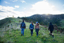 Four Teenagers Walking Up A Hill In The Early Morning
