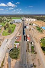 Aerial View Of A Long Grain Train Waiting At A Rural Railway Station