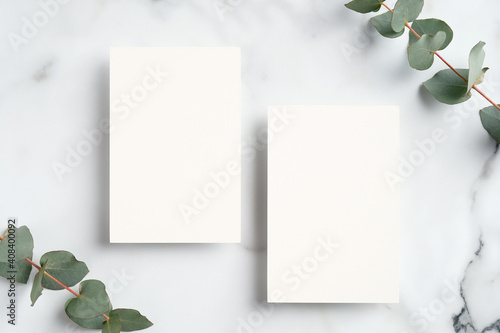 Fototapeta Wedding invitation cards design. Flat lay blank paper card mockup and eucalyptus leaves on marble background obraz