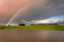 A Vivid Rainbow Arching Over A Dam On Farmland