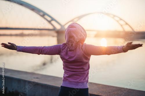 Obraz na plátně Happy female jogger standing and enjoying in beautiful river sunrise