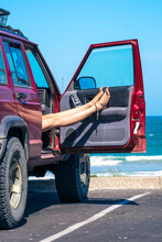 Woman Rests Legs In The Car At A Beach Carpark