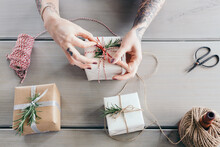 Female Hands Tying Bows On Stylishly Wrapped Christmas Gifts