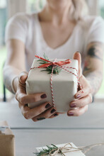 Girl Holding Gift Wrapped Christmas Present To Camera