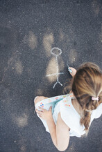 Little Girl Drawing Pictures On The Asphalt With Chalk