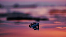 Closeup Shot Of Sunglasses In The Purple Water Of The Sea At Sunset